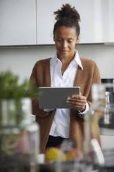 Portrait of businesswoman standing in kitchen using digital tablet - RBF07757