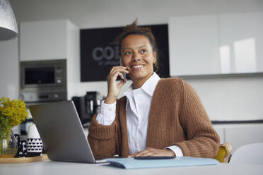 Portrait of smiling businesswoman on the phone in kitchen looking at distance - RBF07760