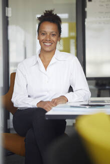 Portrait of smiling businesswoman sitting at desk in office - RBF07766