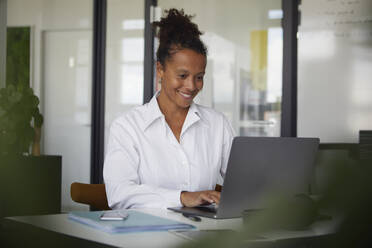 Portrait of smiling businesswoman working on laptop in office - RBF07769