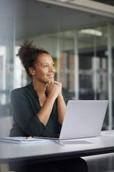 Portrait of smiling businesswoman sitting at desk with laptop looking at distance - RBF07775