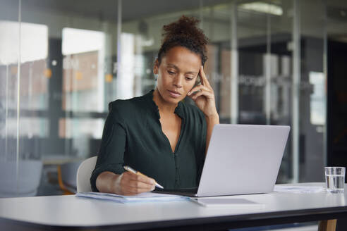 Portrait of pensive businesswoman  working at desk - RBF07778