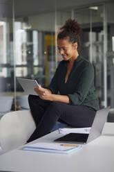 Smiling businesswoman sitting on desk using digital tablet - RBF07781