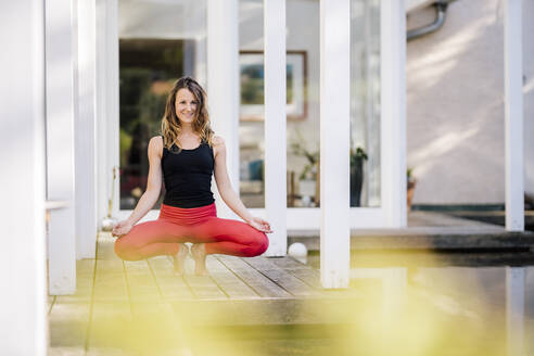 Smiling woman meditating while crouching on hardwood floor against house - DAWF01629