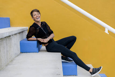 Laughing athletic woman sitting on stairs - LVVF00082