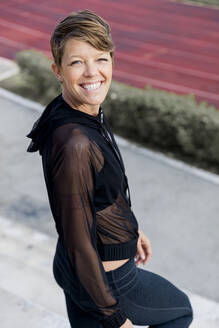 Smiling athletic woman on stairs - LVVF00085