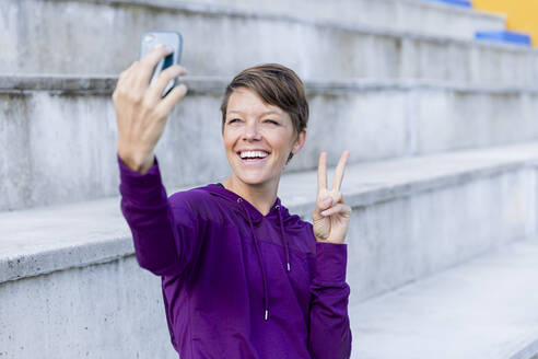 Athletic woman using smartphone and taking a selfie - LVVF00091
