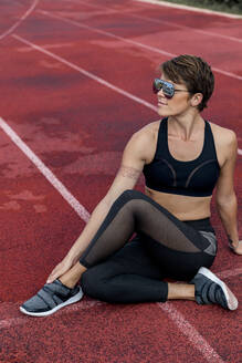 Athletic woman stretching on tartan track, half-spinal twist - LVVF00115