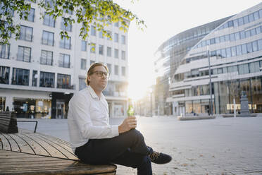 Businessman sitting on a bench in the city at sunset with a bottle of beer - JOSEF00816