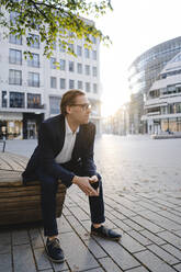 Businessman sitting on a bench in the city - JOSEF00831
