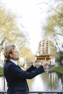 Businessman holding model ship at a channel - JOSEF00837