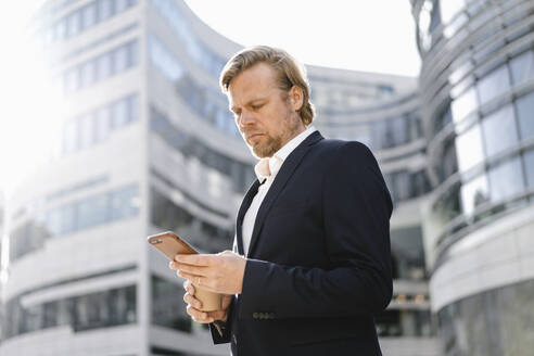 Businessman using smartphone in the city - JOSEF00849