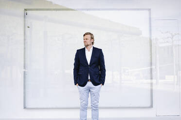Portrait of businessman standing in front of a white wall - JOSEF00864
