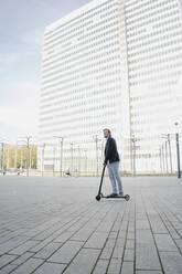 Businessman riding kick scooter on city square - JOSEF00870