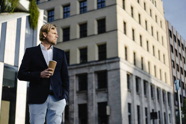 Businessman with takeaway coffee in the city looking around - JOSEF00882