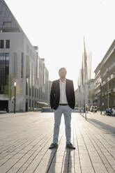 Businessman standing in the city at sunset - JOSEF00888
