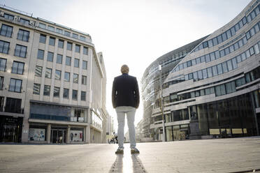 Businessman standing in the city at sunset - JOSEF00903