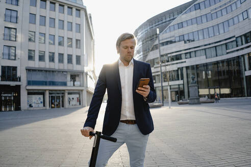 Businessman with kick scooter using smartphone in the city at sunset - JOSEF00912