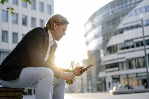 Businessman sitting on a bench in the city at sunset with a bottle of beer and smartphone - JOSEF00918
