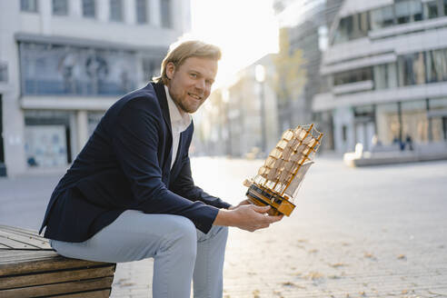 Businessman sitting on a bench in the city holding model ship - JOSEF00924