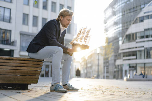 Businessman sitting on a bench in the city holding model ship - JOSEF00927