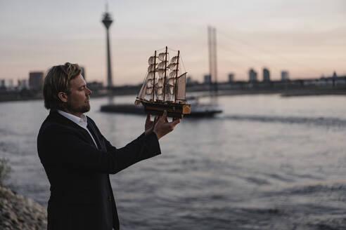 Businessman holding model ship at the riverside at dusk - JOSEF00942