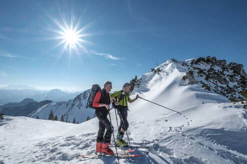 Friends skiing on snowcapped mountain against sky during sunny day, Geigelstein, Bavaria, Germany - HAMF00637