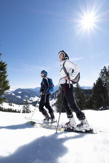 Mother and son skiing on snow covered mountain against sky, Berchtesgaden, Bavaria, Germany - HAMF00640