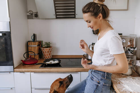 Beautiful woman with messy hands looking at dog while standing in kitchen - OGF00451