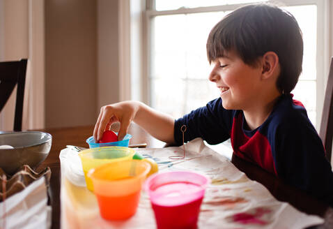 Happy boy dipping an egg into a bowl of dye to color it for Easter. - CAVF85564