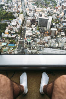 Japan, Osaka Prefecture, Osaka, Legs of man sitting in front of window and looking down at city below - EHF00348