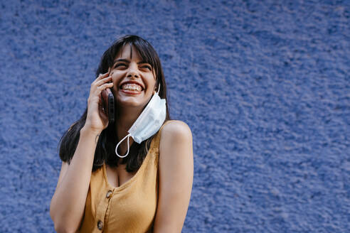 Close-up of smiling woman wearing mask talking over smart phone against wall in city - TCEF00765
