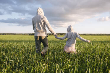 Father and daughter holding hands while walking amidst plants on landscape - EYAF01156