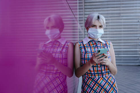 Woman wearing mask using smart phone while standing by pink glass wall - TCEF00773