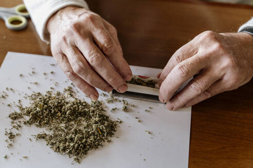 Close-up of retired senior man rolling weed on table - AFVF06693
