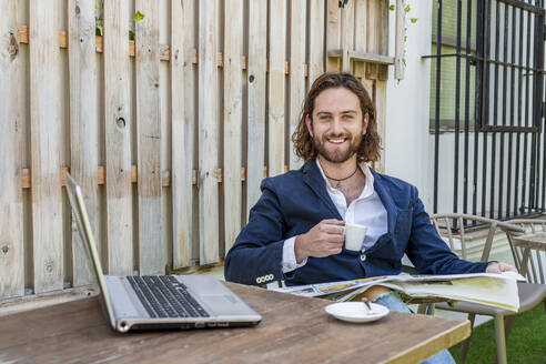 Smiling handsome young businessman reading newspaper while holding coffee cup by laptop at table in cafe - DLTSF00780