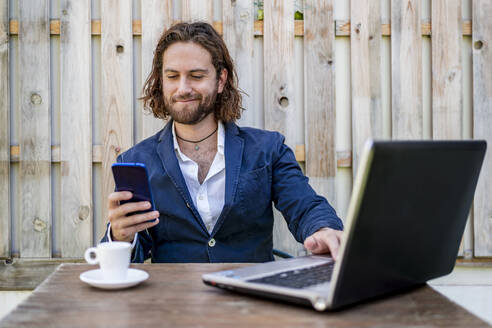 Businessman smirking while using mobile phone sitting at cafe - DLTSF00783