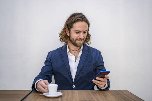 Smiling handsome businessman using smart phone while sitting with espresso at table against white wall in cafe - DLTSF00789
