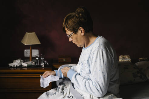 Ill senior woman reading instructions of prescription medicine while sitting on bed at home - XLGF00244