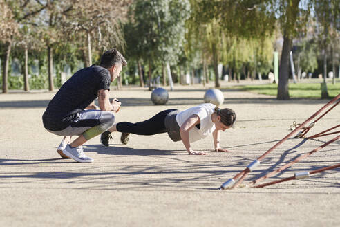Woman during work out with coach in park - JNDF00177