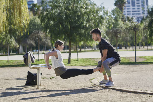 Woman during work out with coach in park - JNDF00180