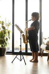 Boy exercising to play the saxophone at home - VABF03091