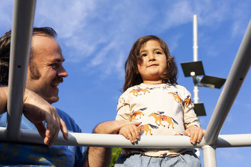 Portrait of little girl and her father on playground - VABF03100