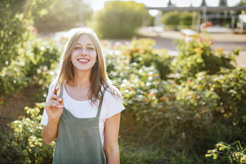 Portrait of smiling young woman in public garden at backlight - TCEF00780