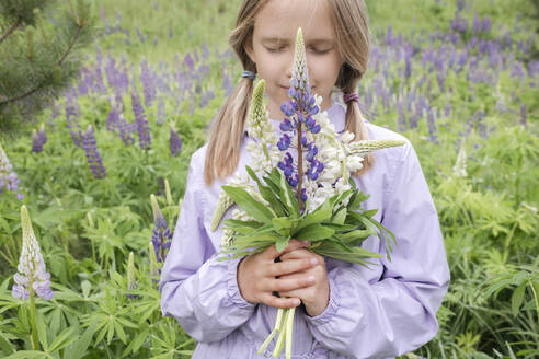 Portrait of girl with eyes closed standing in front of flower field holding bunch of lupines - EYAF01171