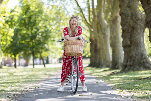 Happy woman leaning on bicycle at public park - WPEF03046