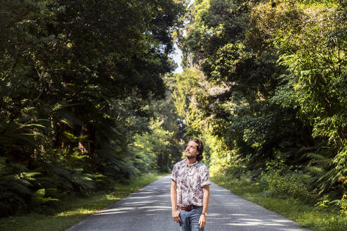 Man walking on road amidst trees in forest - WVF01823