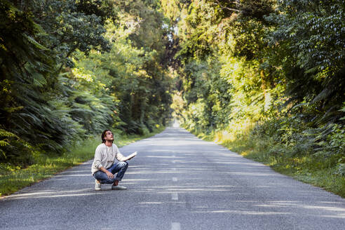 Young man with diary crouching on country road amidst trees - WVF01826