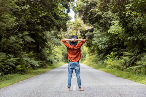 Man standing with hands behind head on country road amidst trees in forest - WVF01835