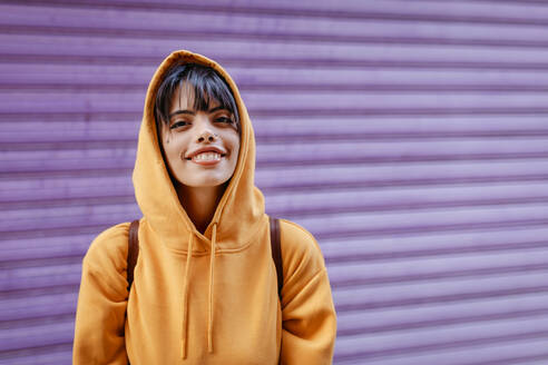 Portrait of young woman with yellow hoodie in front of purple background - TCEF00786